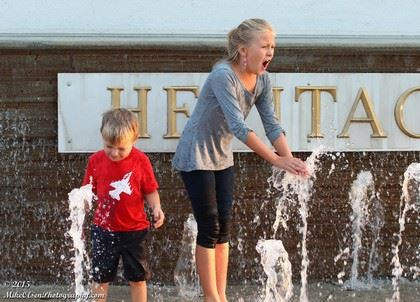 A Boy and a Girl Playing in Spraying Water