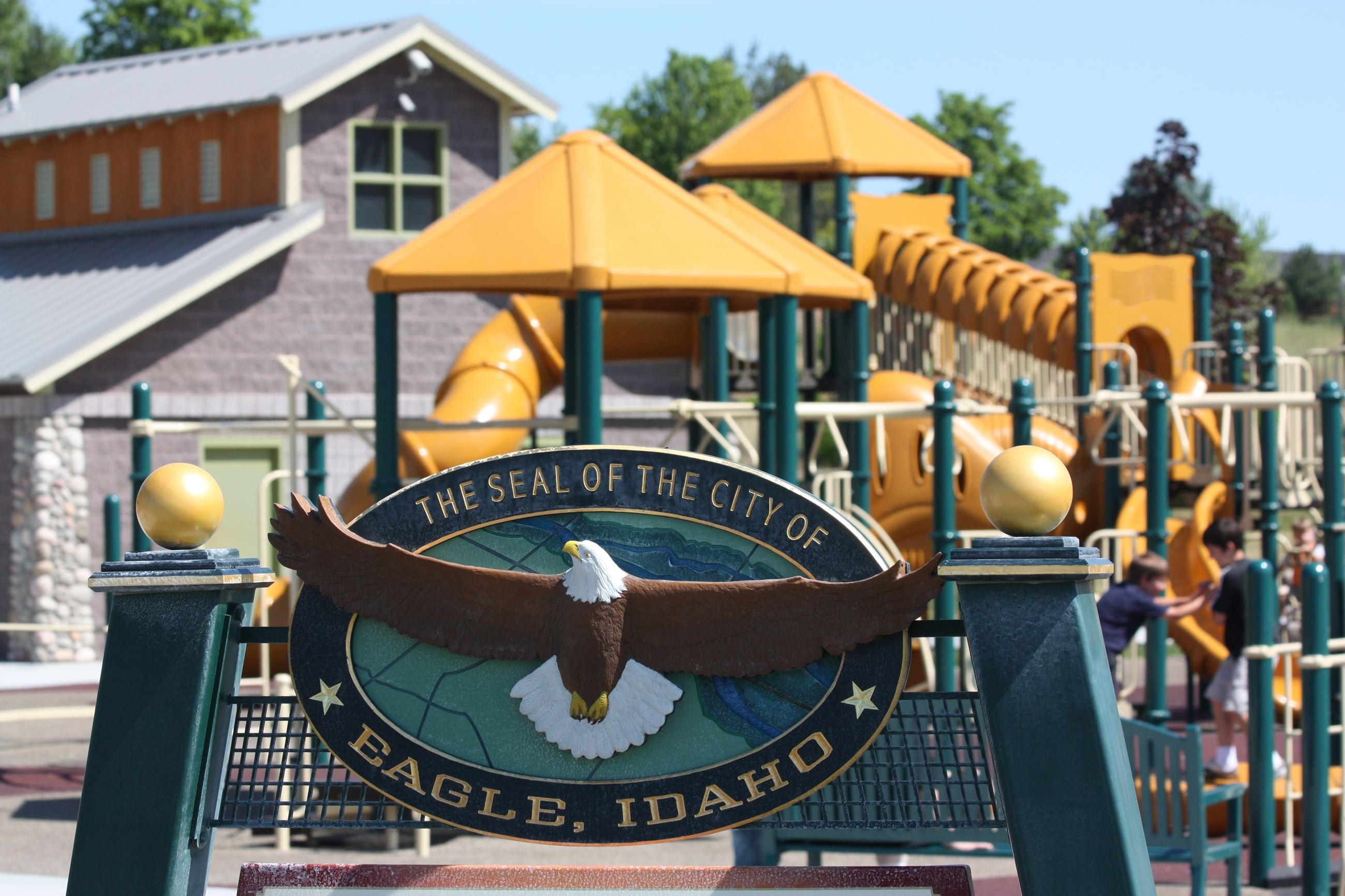 The City of Eagle seal sign in front of the Guerber Park playground.