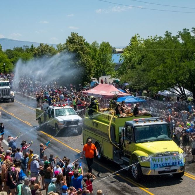 A yellow fire truck sprays the crowd at the wet and wild parade.