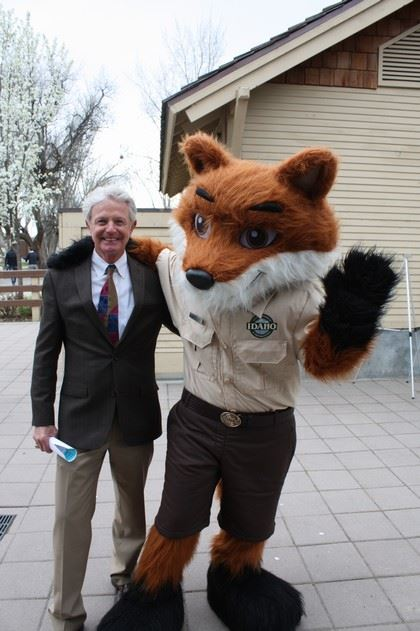 Man in Suit Posing with a Person Wearing a Fox Costume