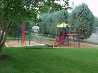 Playground in a Grassy Area and Tennis Court