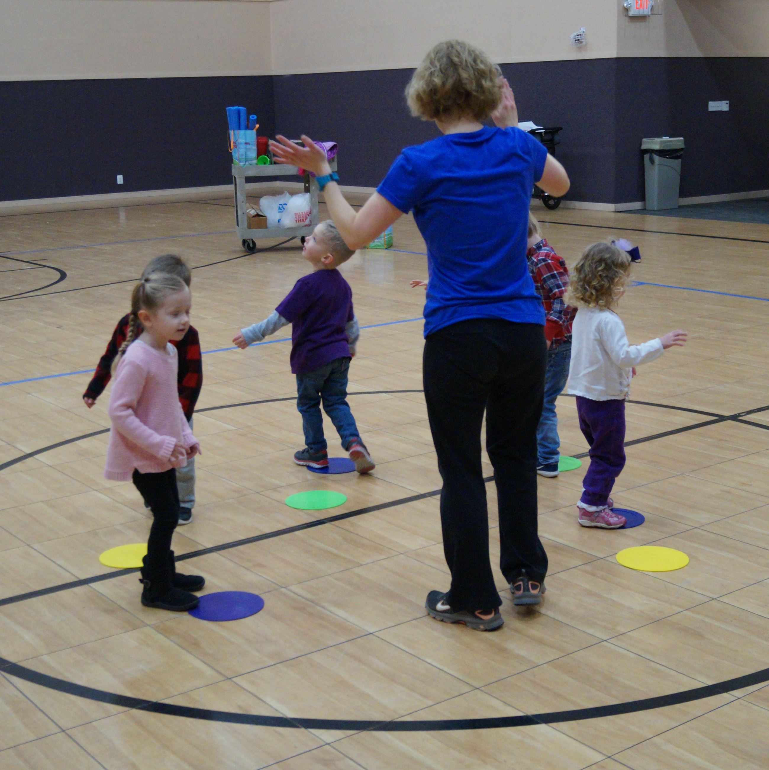 Preschoolers play games in a gymnasium